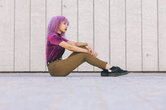 Interracial black woman with colorful afro hair sitting on the g stock photos