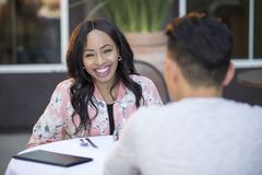 Interracial Blind Date in Outdoor Restaurant. Black female on a blind date with an asian male at an outdoor restaurant. They are sitting and chatting like speed stock photo