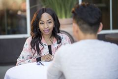 Interracial Blind Date in Outdoor Restaurant. Black female on a blind date with an asian male at an outdoor restaurant.  They are sitting and chatting like speed Royalty Free Stock Images