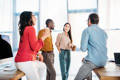 Interracial business colleagues having conversation during coffee break. In office royalty free stock photos
