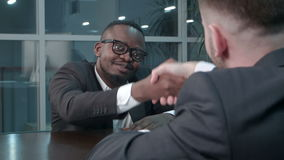 Interracial businessmen shaking hands in business hall, smiling. Close up. Professional shot in 4K resolution. 085. You can use it e.g. in your commercial stock footage
