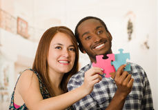 Interracial charming couple embracing friendly, holding up large puzzle pieces and happily interacting having fun Stock Photo