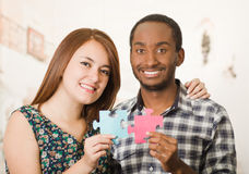 Interracial charming couple embracing friendly, holding up large puzzle pieces and happily interacting having fun Stock Photography