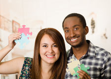 Interracial charming couple embracing friendly, holding up large puzzle pieces and happily interacting having fun Stock Images