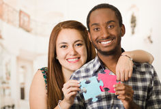 Interracial charming couple embracing friendly, holding up large puzzle pieces and happily interacting having fun Royalty Free Stock Photo