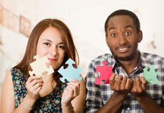 Interracial charming couple holding up large puzzle pieces and happily interacting having fun, blurry studio background Stock Photos