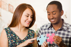 Interracial charming couple holding up large puzzle pieces and happily interacting having fun, blurry studio background Royalty Free Stock Photography