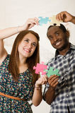 Interracial charming couple wearing casual clothes holding up large puzzle pieces and interacting happily, white studio Stock Images