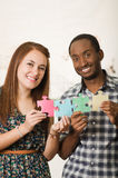 Interracial charming couple wearing casual clothes holding up large puzzle pieces and interacting happily, white studio Royalty Free Stock Photography