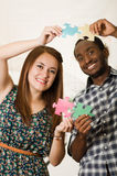 Interracial charming couple wearing casual clothes holding up large puzzle pieces and interacting happily, white studio Stock Image