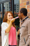 Interracial charming couple wearing casual clothes interacting happily and sharing an ice cream Royalty Free Stock Photo