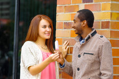 Interracial charming couple wearing casual clothes interacting happily and sharing an ice cream Stock Images