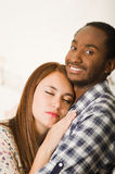 Interracial charming couple wearing casual clothes posing while embracing intimately, she has eyes closed and him Stock Photos