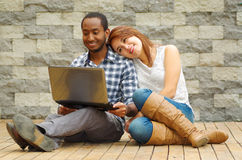 Interracial charming couple wearing casual clothes sitting down on wooden surface lookin at laptop together, in front of. Grey brick wall Royalty Free Stock Photo