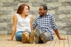 Interracial charming couple wearing casual clothes sitting on wooden surface posing for camera staring at each other. Grey brick wall background Royalty Free Stock Photography