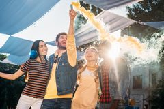 interracial cheerful young friends with colorful smoke bomb stock images