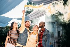 interracial cheerful young friends with colorful smoke bomb stock photos