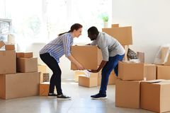 Interracial couple carrying box indoors. Moving into new house royalty free stock photo
