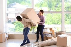 Interracial couple carrying box indoors. Moving into new house stock photography