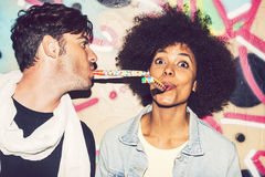Interracial couple celebrating and playing with party blowers Royalty Free Stock Photography