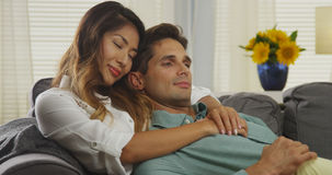 Interracial couple cuddling on couch. At home royalty free stock photos