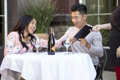 Dating Couple Paying at a Restaurant. Interracial couple on a date paying for a restaurant tab with a waitress. They are in an outdoor cafe handling the payment Stock Images