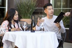 Dating Couple Paying at a Restaurant. Interracial couple on a date paying for a restaurant tab with a waitress. They are in an outdoor cafe handling the payment Stock Photo