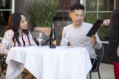 Dating Couple Paying at a Restaurant. Interracial couple on a date paying for a restaurant tab with a waitress. They are in an outdoor cafe handling the payment Stock Photography