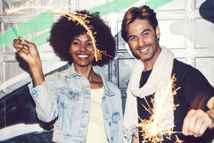 Interracial couple having fun with bengal lights Royalty Free Stock Image