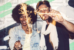 Interracial couple having fun with bengal lights Royalty Free Stock Photography