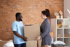 Interracial couple holding box indoors. Moving into new house stock photos
