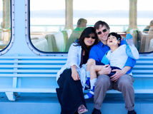 Interracial couple holding disabled son on ferry boat deck. Smiling multiracial, interracial couple holding disabled son on ferry boat deck. Child has cerebral Royalty Free Stock Photos
