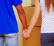 Interracial couple holding hands, seen from behind with stacked boxes in background, moving in concept royalty free stock images