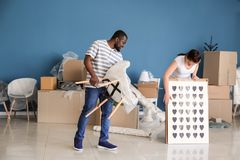 Interracial couple with interior items and carton boxes in room. Moving into new house royalty free stock photography