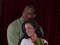 Interracial couple in love. Handsome young African-American man embraces beautiful caucasian girlfriend from behind while she rests her head on his chest Royalty Free Stock Photo