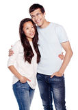 Interracial couple in love. Portrait of young interracial couple, hispanic men and asian girl, wearing jeans, standing, hugging and smiling isolated on white Royalty Free Stock Photography