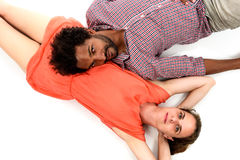 Interracial couple is lying on the floor embracing their love. African American black men wearing stripped shirt is in love with Caucasian white women wearing Stock Photo