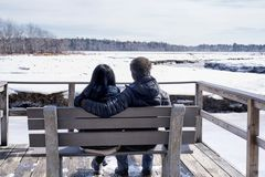 Interracial couple in Maine winter landscape. A mixed ethnic couple sitting on a bench looking out over the frozen landscape within the Rachel Carson National royalty free stock photography