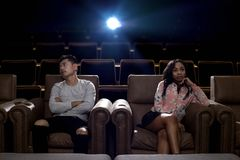 Interracial couple on a movie theater date. Young interracial dating couple in a movie theater watching a show.  The men is asian and the women is black.  They Royalty Free Stock Photo