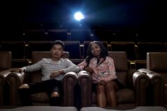 Interracial couple on a movie theater date. Young interracial dating couple in a movie theater watching a show. The men is asian and the women is black stock image