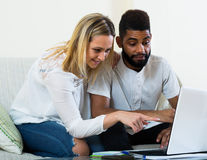 Interracial couple near laptop Royalty Free Stock Images
