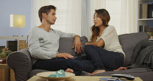 Interracial couple talking on couch Stock Photo