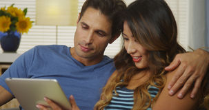 Interracial couple talking about the news they're reading on tablet Royalty Free Stock Images