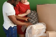 Interracial couple unpacking box indoors. Moving into new house stock photography