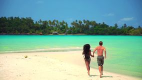 Slow motion footage: interracial happy couple enjoy honeymoon on the tropical beach at sunny summer day. Interracial couple white Caucasian man and tanned Asian stock video footage