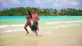 Slow motion video: Happy couple enjoy honeymoon on the tropical beach at sunny summer day. Interracial couple white Caucasian man and tanned Asian girl close-up stock footage