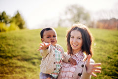 Interracial family. Caucasian mother and her african american son having fun in park royalty free stock images