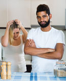 Interracial family couple with serious faces quarrelling in kitc Stock Photos