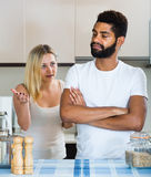 Interracial family couple with serious faces quarrelling in kitc Stock Images
