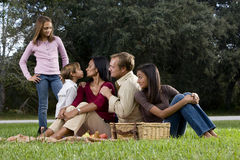Interracial family of five having picnic in park stock images